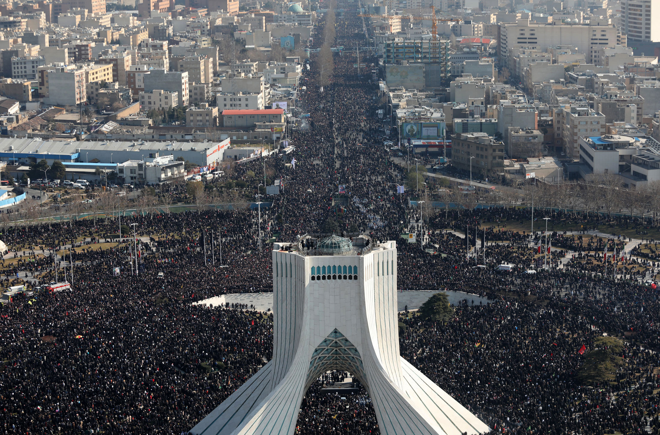 In this photo released by the official website of the Office of the Iranian Supreme Leader, mourners attend a funeral ceremony for Iranian Gen. Qassem Soleimani and his comrades, who were killed in Iraq in a U.S. drone attack on Friday, Jan. 3 as Azadi (freedom) tower is seen in the foreground, in Tehran, Iran, Monday, Jan. 6, 2020. The funeral for Soleimani drew a crowd said by police to be in the millions in the Iranian capital, filling thoroughfares and side streets as far as the eye could see. (Office of the Iranian Supreme Leader via AP)