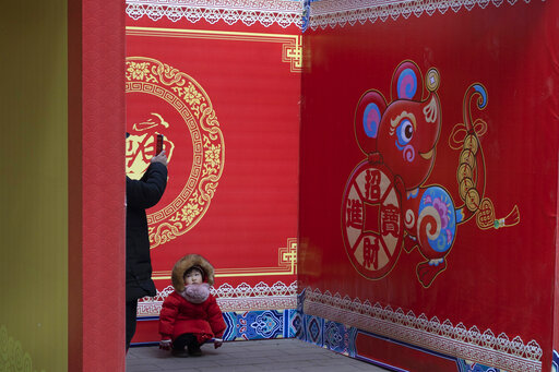 A child squats near a depiction of a rat ahead of the Chinese Lunar New Year celebrations in Beijing on Thursday, Jan. 16, 2020. The world's largest annual migration begins this week in China with millions of Chinese traveling to their hometowns to celebrate the Lunar New Year on Jan. 25 this year which marks the Year of the Rat on the Chinese zodiac. (AP Photo/Ng Han Guan)