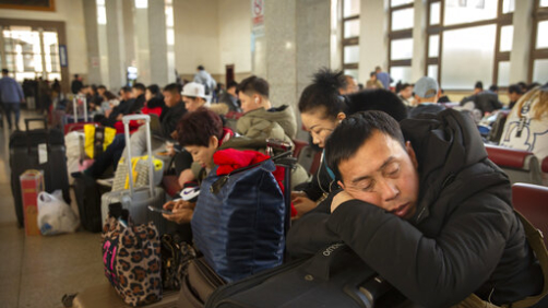 A traveler rests on his suitcase in a waiting room at the Beijing Railway Station in Beijing, Friday, Jan. 17, 2020. As the Lunar New Year approached, Chinese travelers flocked to train stations and airports Friday to take part in a nationwide ritual: the world's biggest annual human migration. (AP Photo/Mark Schiefelbein)