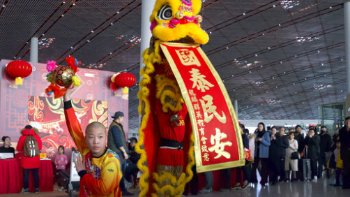 Travelers watch a lion dance performance at Beijing Capital International Airport in Beijing, Friday, Jan. 17, 2020. As the Lunar New Year approached, Chinese travelers flocked to train stations and airports Friday to take part in a nationwide ritual: the world's biggest annual human migration. (AP Photo/Ng Han Guan)