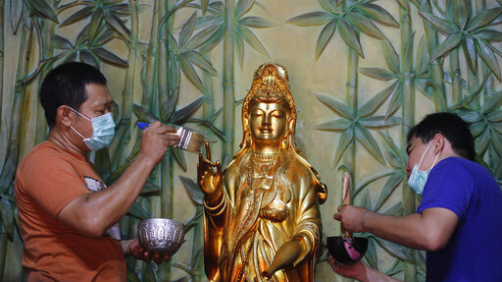 Indonesians of Chinese descent wash a statue of Chinese god in preparation for the Lunar New Year celebration at a temple in Bali, Indonesia, Saturday, Jan. 18, 2020. Chinese communities in the world's most populous Muslim country are gearing up to celebrate the start of the year of the rat which falls on Jan. 25. (AP Photo/Firdia Lisnawati)