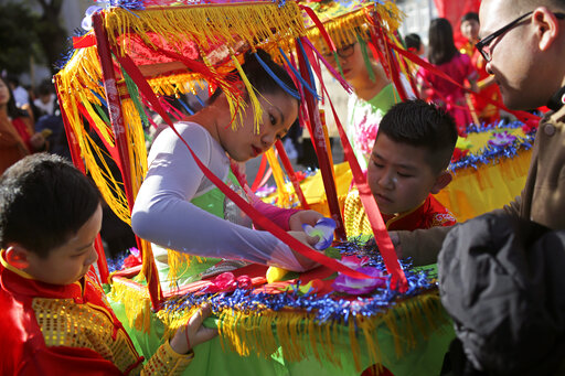 A girl fixes a flower on her costume while waiting to start in a parade opening the Chinese New Year celebrations in Lisbon, Saturday, Jan. 18, 2020. The Chinese Lunar New Year of the Rat, the first of the 12 animals of the Chinese Zodiac, officially begins on Jan. 25. (AP Photo/Armando Franca)