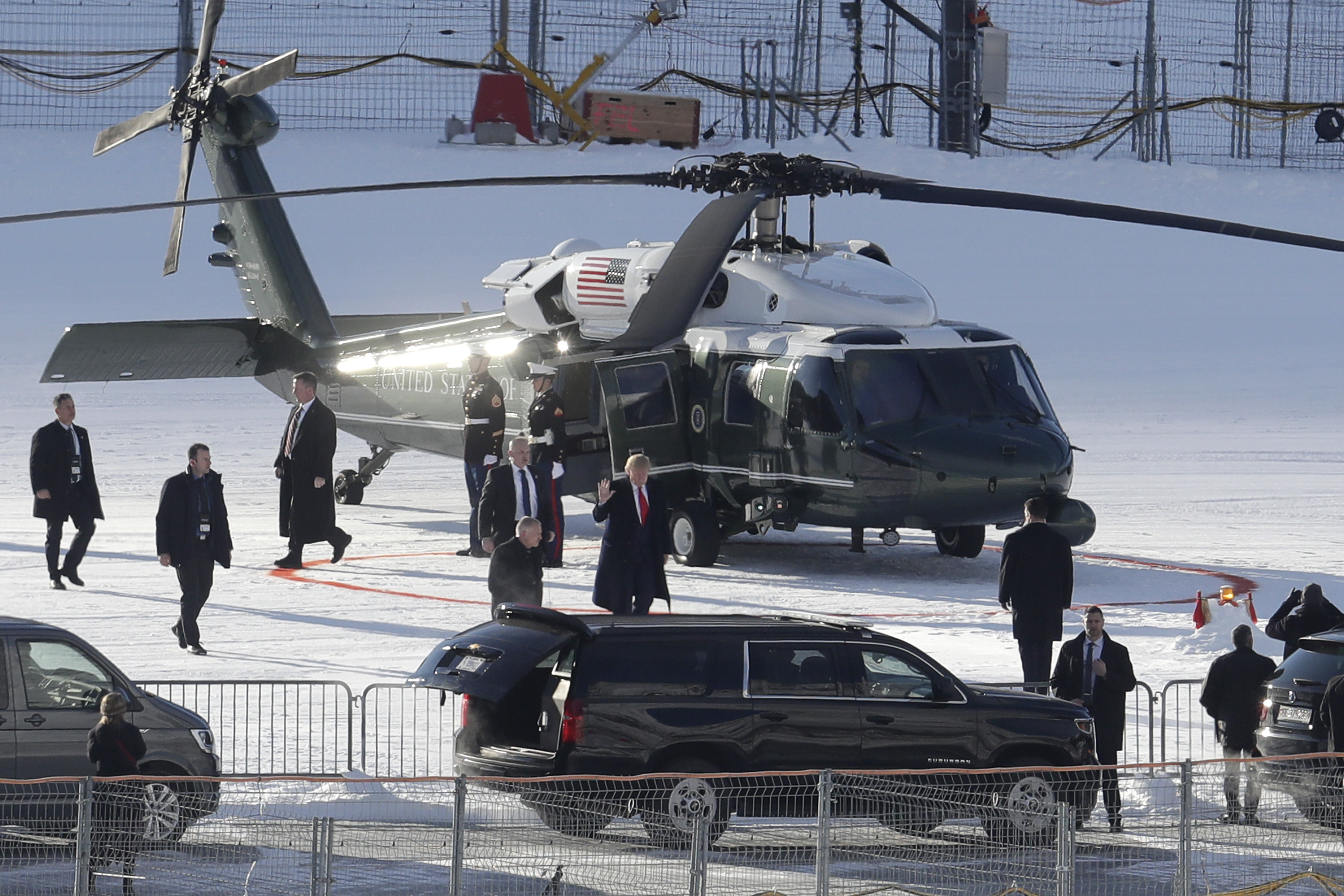 US President Donald Trump, center with red tie, waves as he arrives in Davos, Switzerland on Marine One, Tuesday, Jan. 21, 2020. President Trump arrived in Switzerland on Tuesday to start a two-day visit to the World Economic Forum. (AP Photo/Michael Probst)