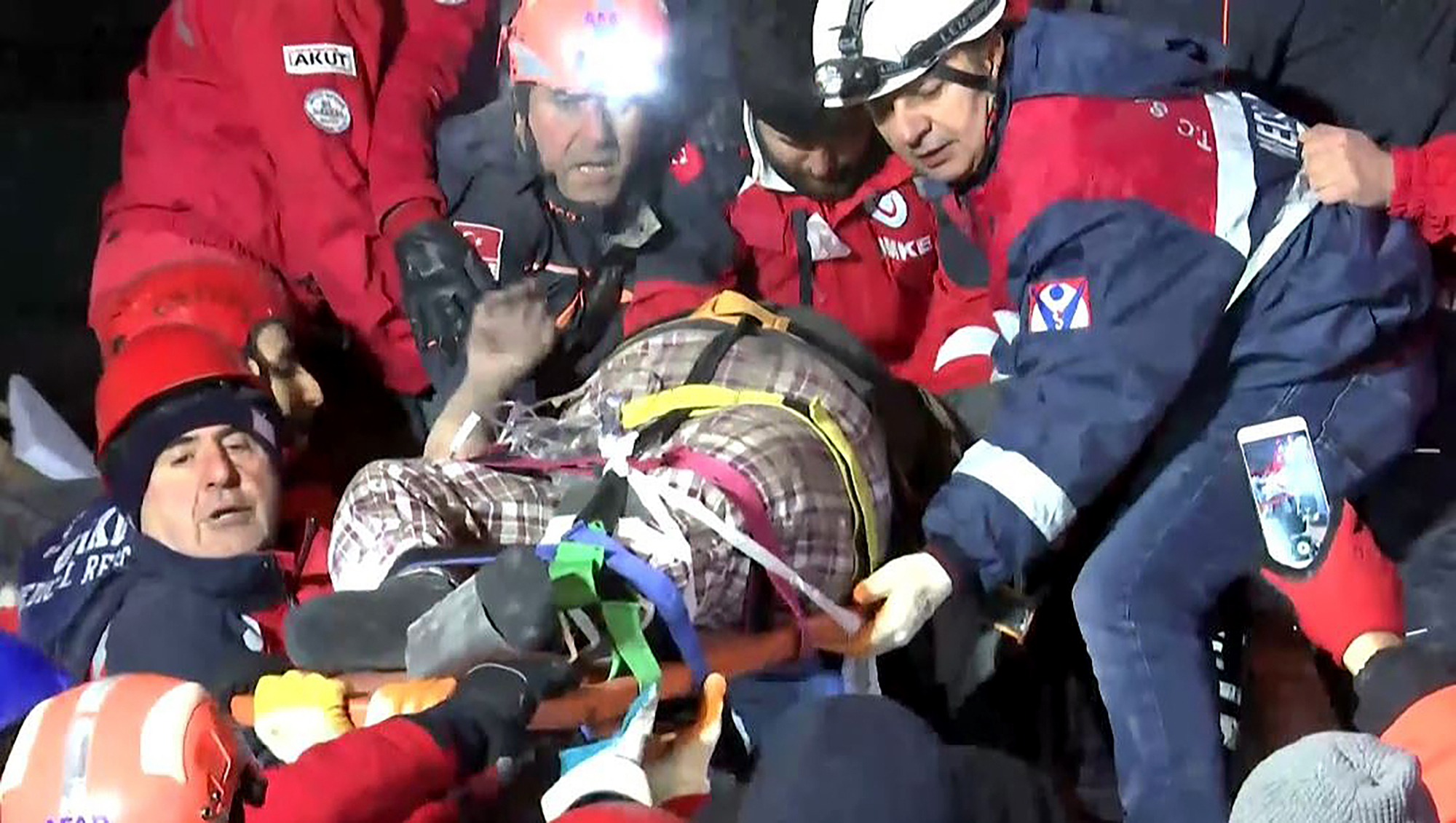Rescue workers carry a wounded person after they rescued him from the debris of a collapsed building following a strong earthquake in Elazig in the eastern Turkey, Saturday, Jan. 25, 2020. The earthquake rocked eastern Turkey on Friday, causing some buildings to collapse and killing scores of people, Turkish officials said. (IHA via AP)