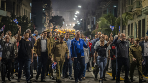 Cuba's President Miguel Diaz Canel, center right, and Raul Castro, center, hold flags as they take part in a march marking the 167th anniversary of the birth of Cuba's national independence hero Jose Marti, in Havana, Cuba, Monday, Jan. 27, 2020. (AP Photo/Ramon Espinosa)