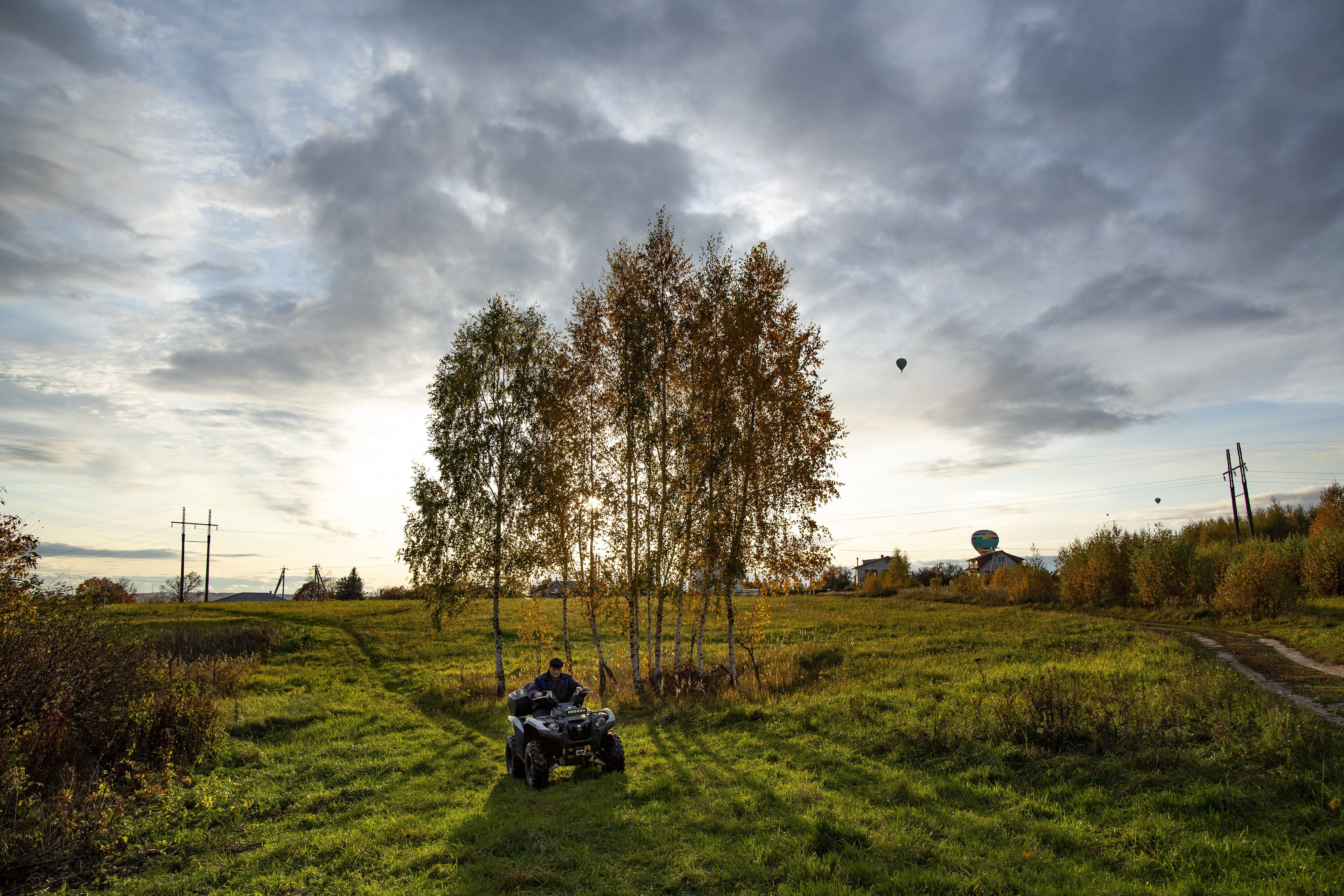 A man rides an all-terrain vehicle through an autumn field during sunset near Peremilovo village, 65 km (40,6 miles) north of Moscow, Russia, Saturday, Oct. 5, 2019. (AP Photo/Alexander Zemlianichenko)
