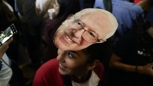 Michelle Nicoleq wears a Bernie Sanders mask as she attends a campaign event for Democratic presidential candidate Sen. Bernie Sanders, I-Vt., in San Antonio, Saturday, Feb. 22, 2020. (AP Photo/Eric Gay)