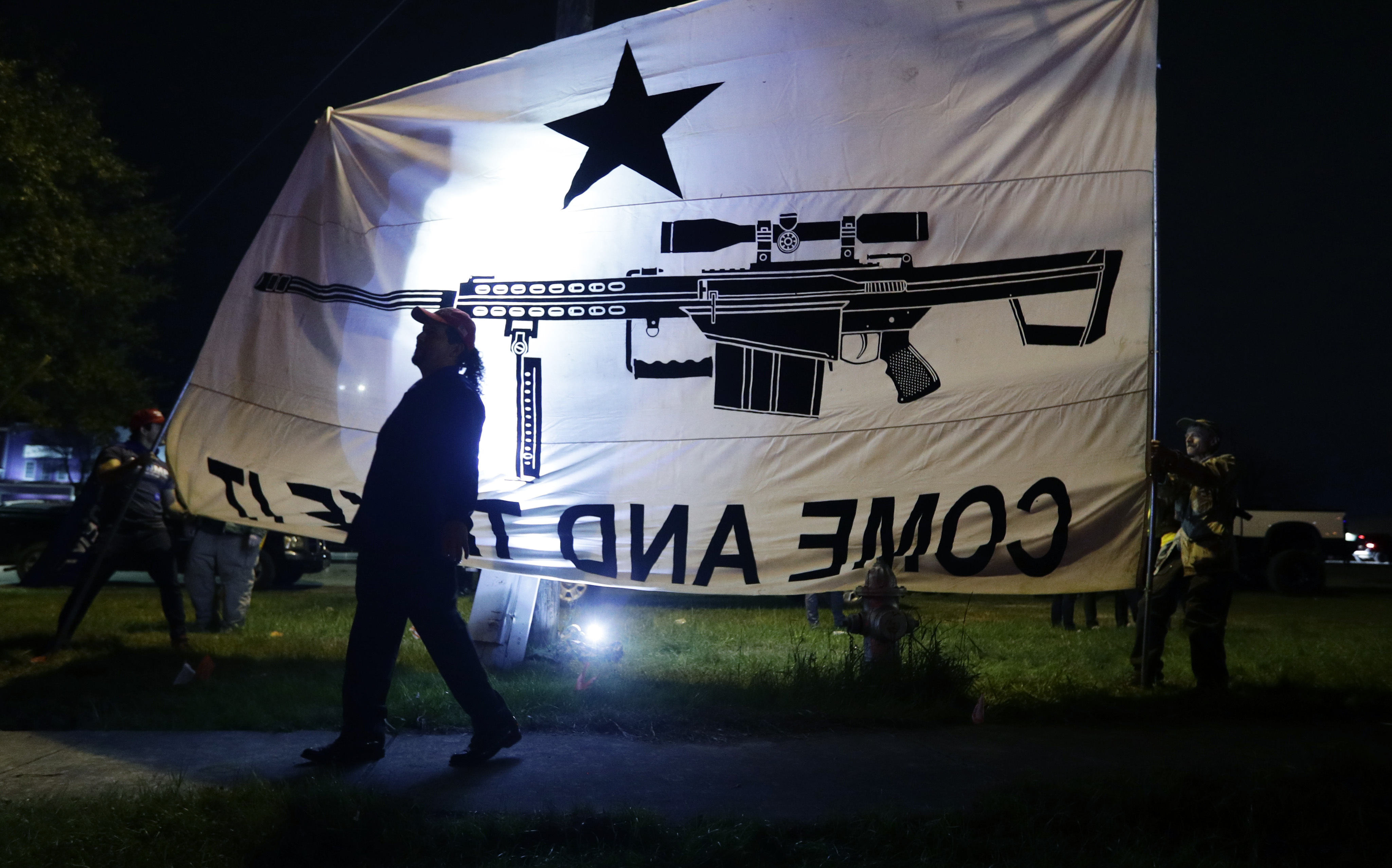 Supporters of President Donald Trump hold flags and banners outside of a campaign event for Democratic presidential candidate Sen. Bernie Sanders in San Antonio, Saturday, Feb. 22, 2020. (AP Photo/Eric Gay)