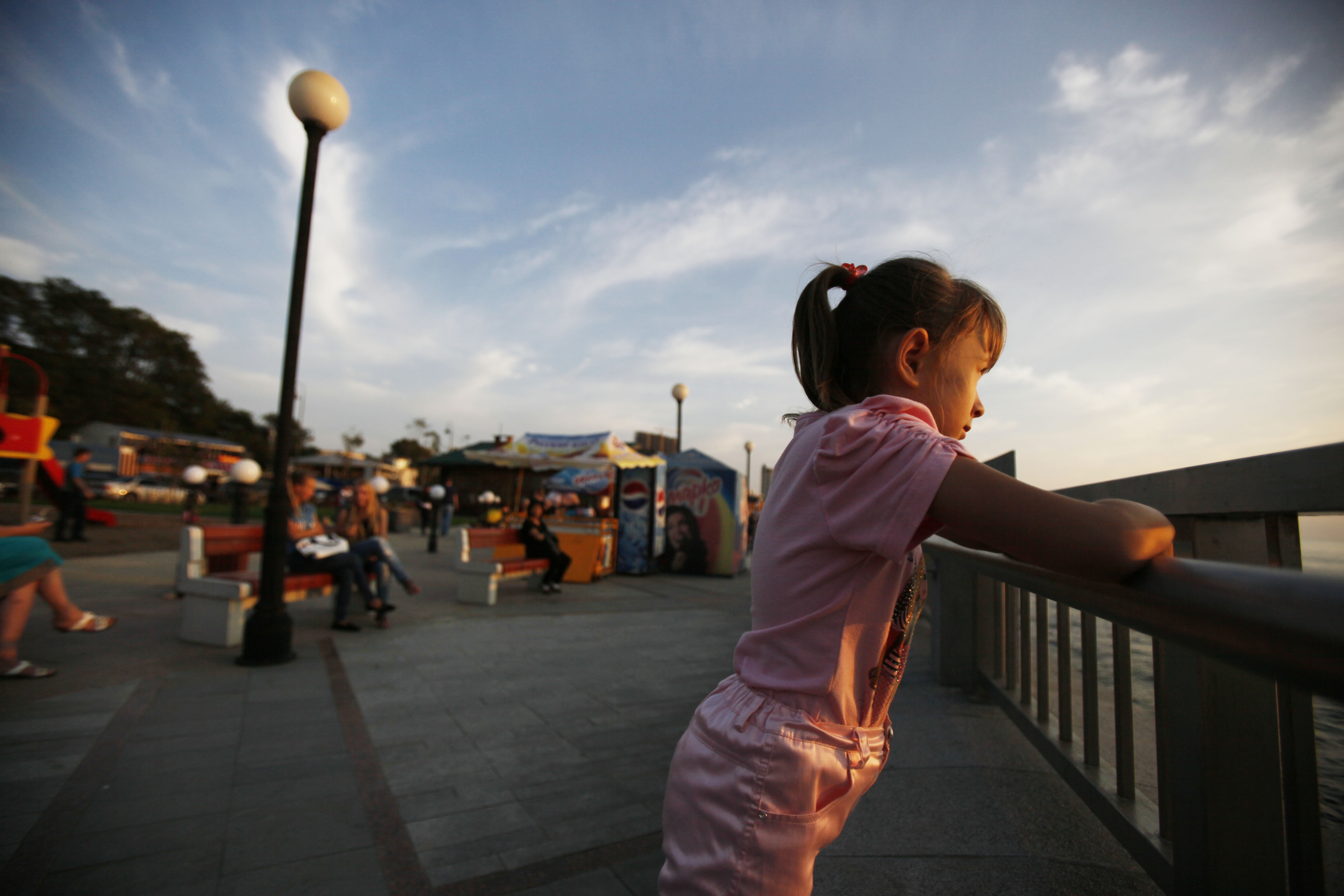 A young girl looks out from a waterfront walkway in Vladivostok, Russia, Monday, Sept. 10, 2012. (AP Photo/Greg Baker)