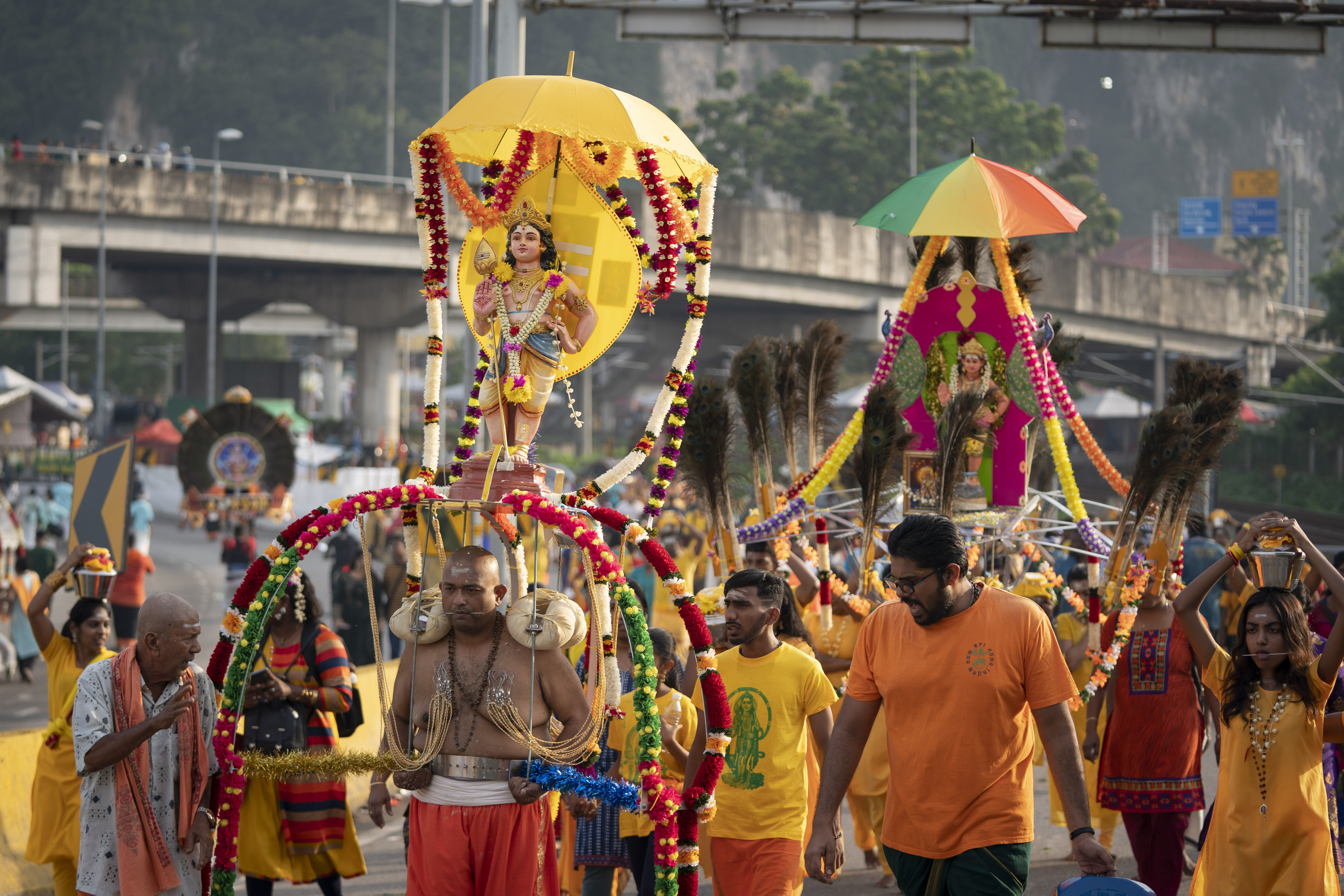 Giant Kavadi offering cages are carried by Hindu devotees in a procession during the Thaipusam festival at Batu Caves, outskirts of Kuala Lumpur, Saturday, Feb. 8, 2020. Thaipusam, which is celebrated in honor of Hindu god Lord Murugan, is an annual procession by Hindu devotees seeking blessings, fulfilling vows and offering thanks. (AP Photo/Vincent Thian)