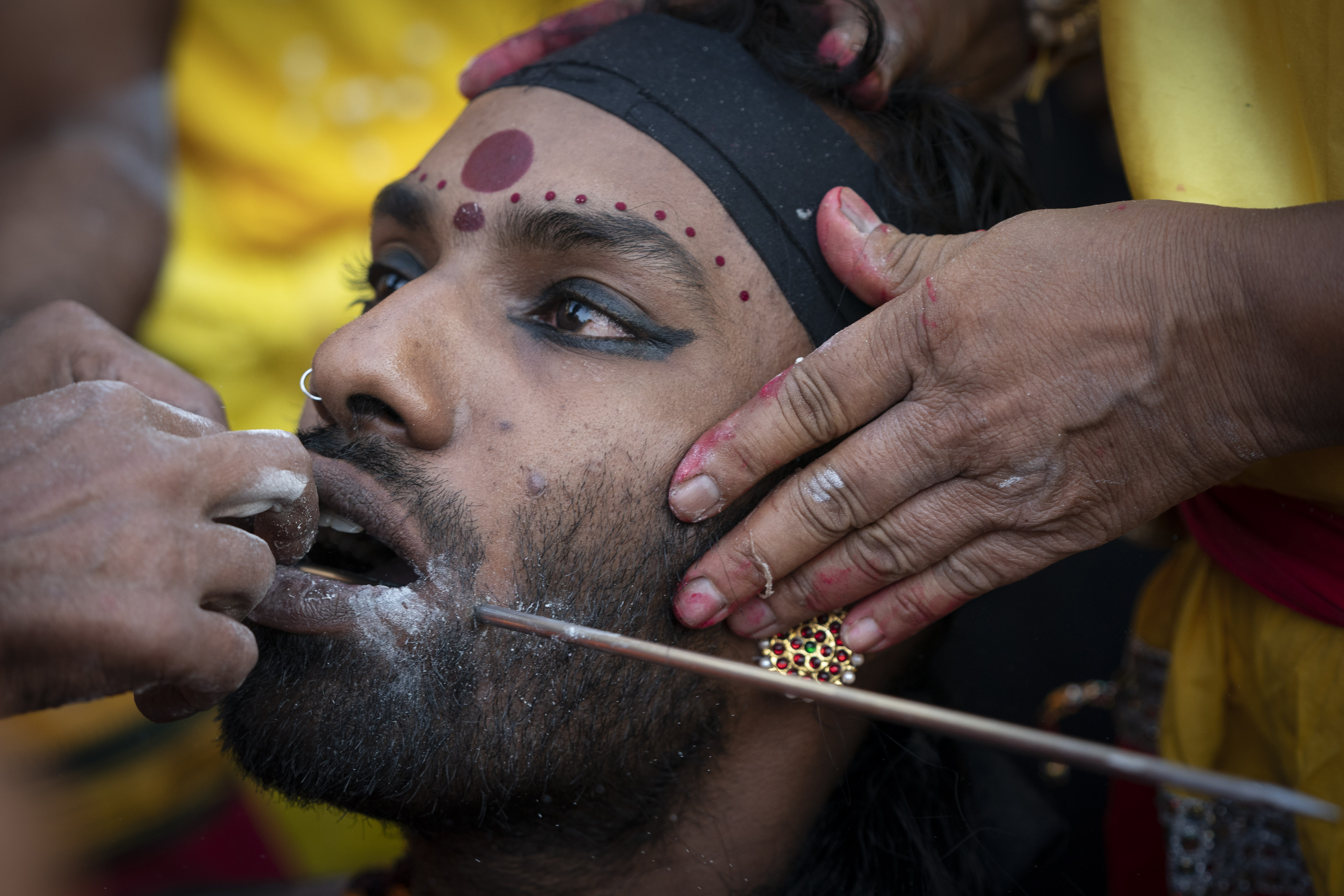 A Hindu devotee gets his tongue pierced with a metal rod during the Thaipusam festival at Batu Caves, outskirts of Kuala Lumpur, Saturday, Feb. 8, 2020. Thaipusam, which is celebrated in honor of Hindu god Lord Murugan, is an annual procession by Hindu devotees seeking blessings, fulfilling vows and offering thanks. (AP Photo/Vincent Thian)