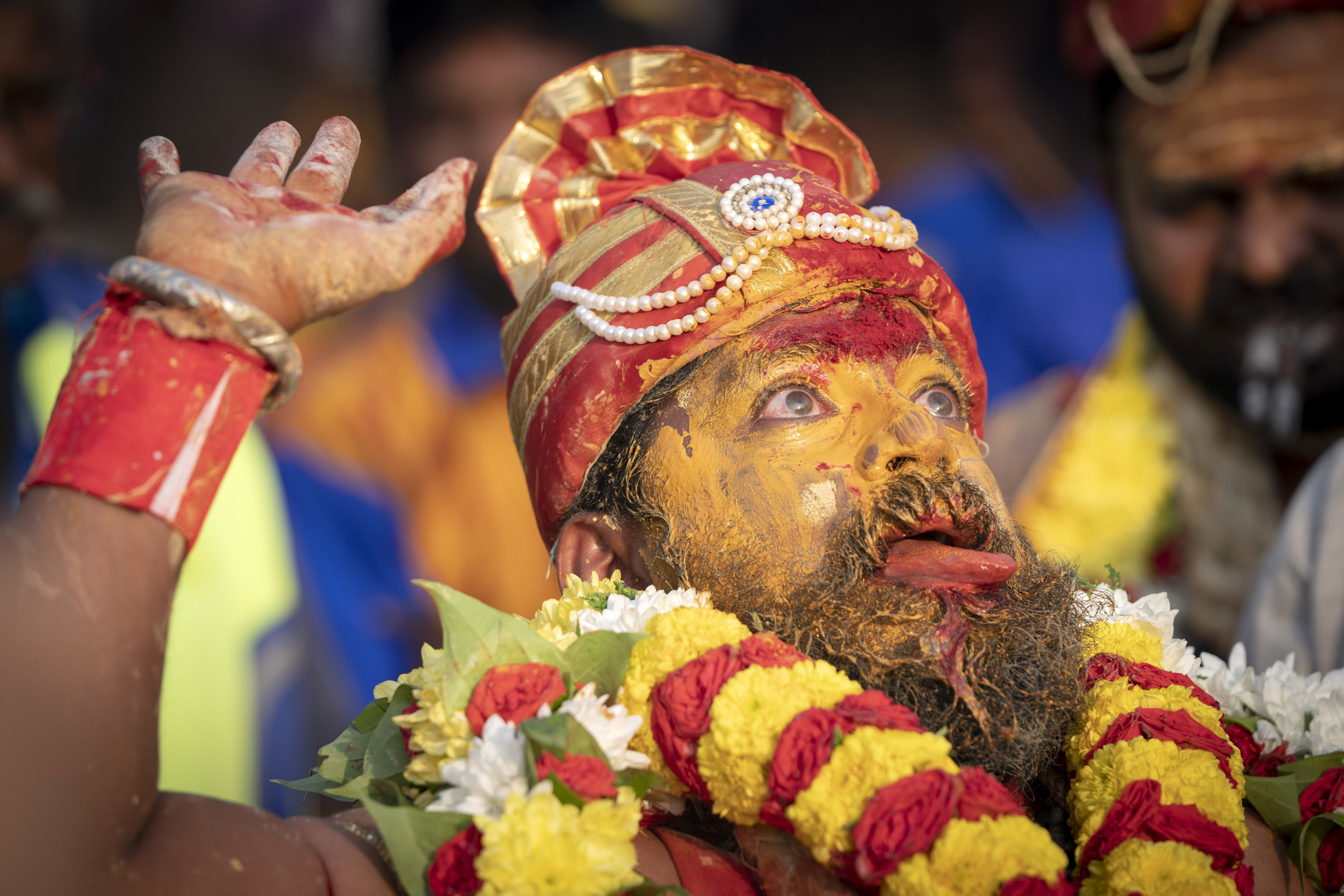 A Tamil Hindu priest has antiseptic powder on his face in a procession during the Thaipusam festival at Batu Caves, outskirts of Kuala Lumpur, Saturday, Feb. 8, 2020. Thaipusam, which is celebrated in honor of Hindu god Lord Murugan, is an annual procession by Hindu devotees seeking blessings, fulfilling vows and offering thanks. (AP Photo/Vincent Thian)