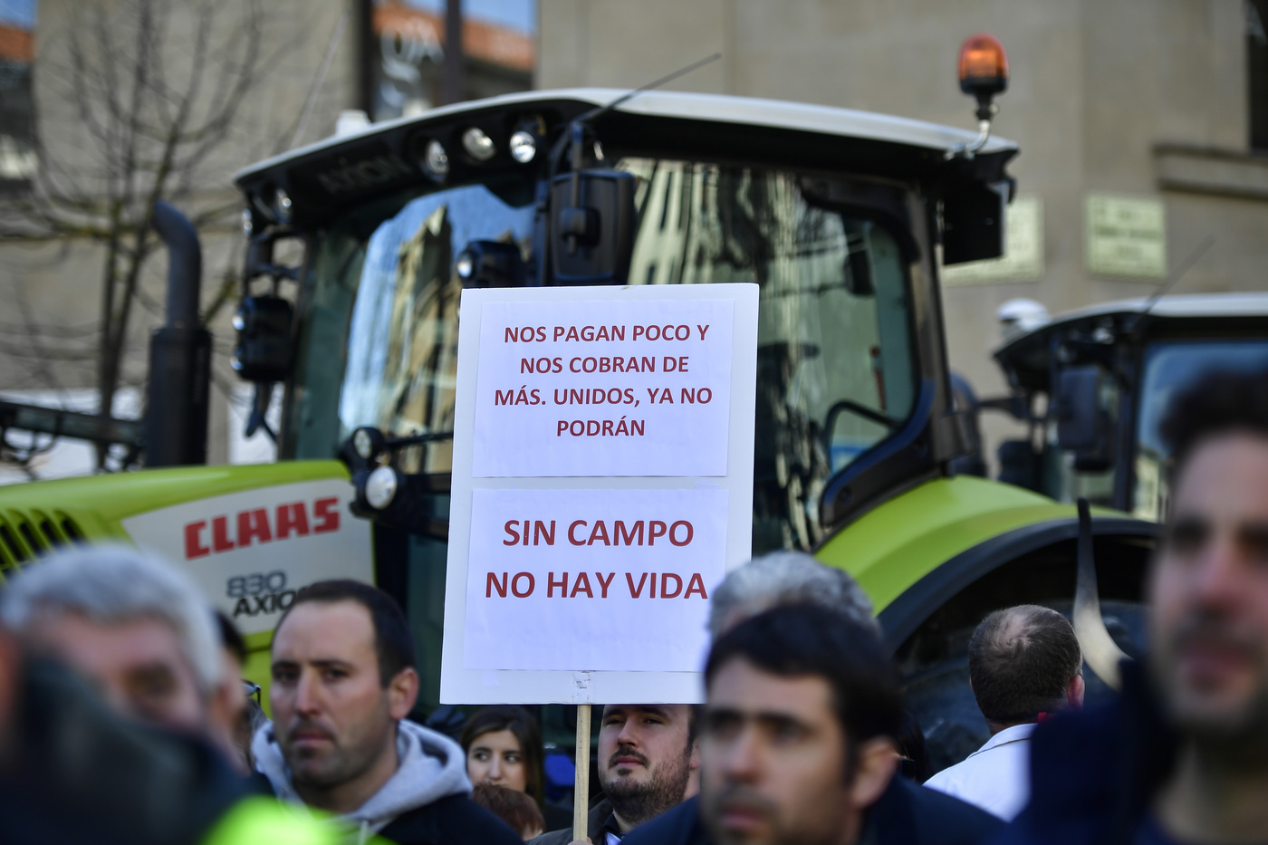 A man holds up a banner reading, ''They pay us little and they charge us more. If we are united they will can no longer. Without fields there is no life'' during a protest in Pamplona, northern Spain, Wednesday, Feb. 19, 2020. Farmers across Spain are taking part in mass protests over what they say are plummeting incomes for agricultural workers. (AP Photo/Alvaro Barrientos)