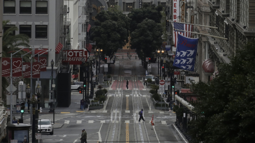 Pedestrians cross an empty Powell Street in San Francisco, Sunday, March 29, 2020. Californians endured a weekend of stepped-up restrictions aimed at keeping them home as much as possible while hospitals and health officials scrambled Sunday to ready themselves for a week that could see the feared dramatic surge in coronavirus cases.  (AP Photo/Jeff Chiu)