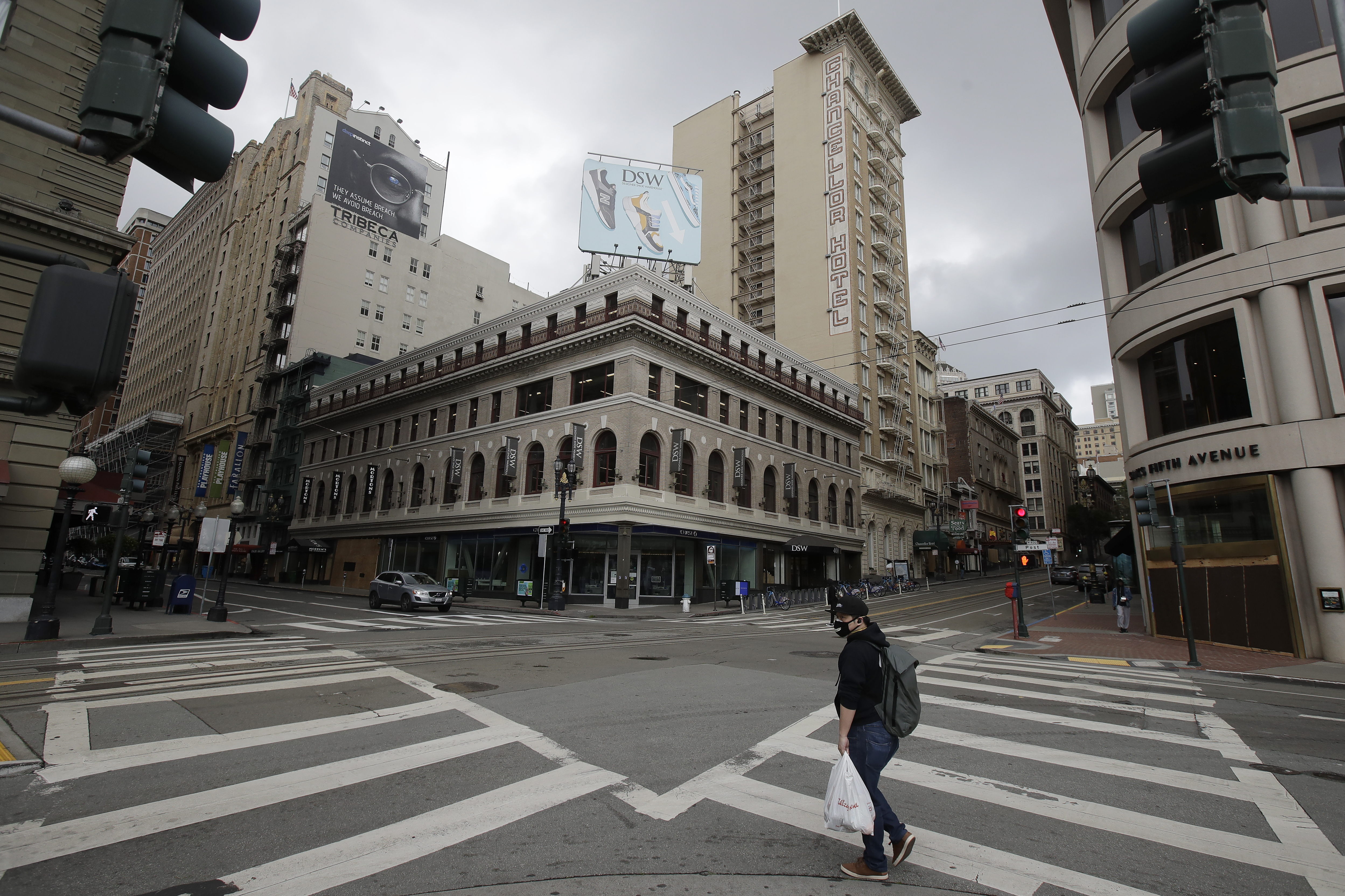 A man wears a mask while crossing an empty intersection in the Union Square retail area of San Francisco, Sunday, March 29, 2020. Californians endured a weekend of stepped-up restrictions aimed at keeping them home as much as possible while hospitals and health officials scrambled Sunday to ready themselves for a week that could see the feared dramatic surge in coronavirus cases. (AP Photo/Jeff Chiu)