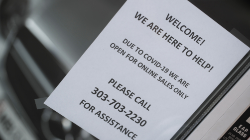 In this Sunday, April 5, 2020, photograph, a sign hangs in the front door of a Mercedes Benz dealership in Littleton, Colo. (AP Photo/David Zalubowski)