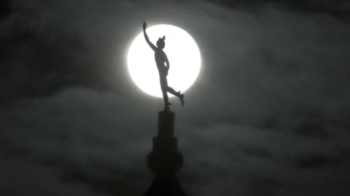 A supermoon rises behind a statue of the Roman god Mercury mounted on top of a hotel tower, Tuesday, April 7, 2020, in Nashville, Tenn. (AP Photo/Mark Humphrey)