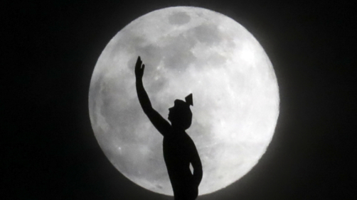 A supermoon rises behind a statue of the Roman god Mercury mounted on top of a hotel tower Tuesday, April 7, 2020, in Nashville, Tenn. (AP Photo/Mark Humphrey)