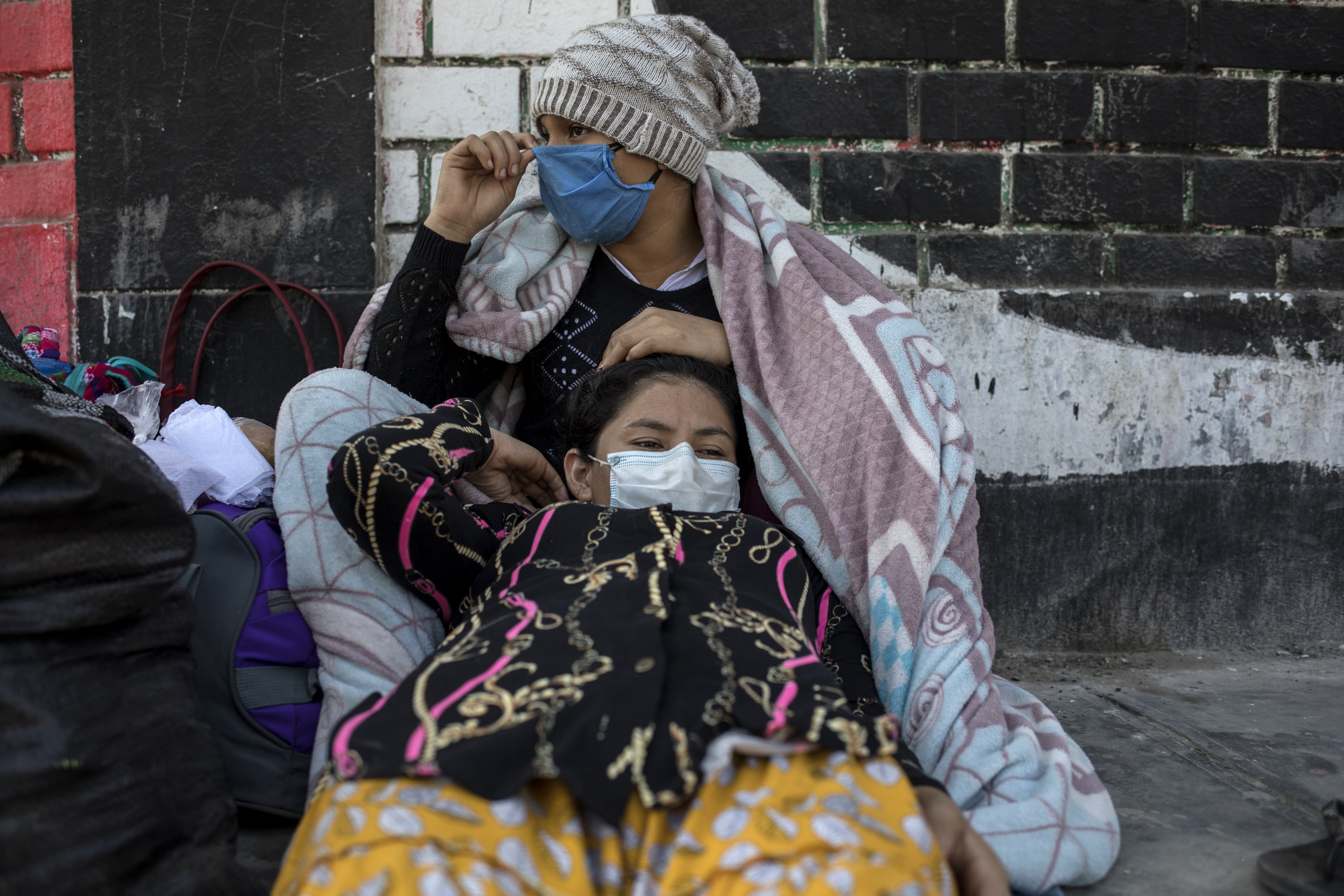 Milka Segura, 15, rests with her sister Ruth, 20, in a makeshift camp on the side of a highway, Tuesday, April 21, 2020, in Lima, Peru. After not being allowed to leave the capital because the strict quarantine rules amid the new coronavirus pandemic, day laborers and informal workers are now allowed to travel home. (AP Photo/Rodrigo Abd)