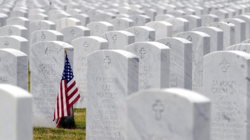 this May 22, 2020 photo, a U.S. flag decorates a veteran's grave at Alabama National Cemetery in Montevallo, Ala. Because of the coronavirus pandemic, the government has banned public ceremonies and the mass placement of flags on graves at the country's 142 national cemeteries. With almost 4.9 million people interred in the cemeteries, thousands would attend memorial events and help mark graves with flags during a typical Memorial Day weekend. (AP Photo/Jay Reeves)