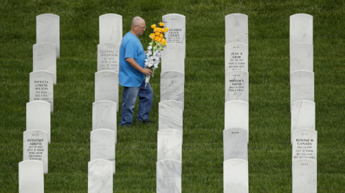 A man looks for a grave while visiting Leavenworth National Cemetery Saturday, May 23, 2020 in Leavenworth, Kan. Several people said they made their annual visit to the cemetery today instead of Memorial Day to beat the crowd and minimize the chance of catching COVID-19. (AP Photo/Charlie Riedel)