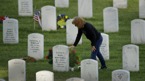 Pam Barba pauses at her parent's grave while visiting Leavenworth National Cemetery Saturday, May 23, 2020 in Leavenworth, Kan. Barba said she decided to visit to the cemetery today instead of Memorial Day to beat the crowd and minimize the chance of catching COVID-19. (AP Photo/Charlie Riedel)