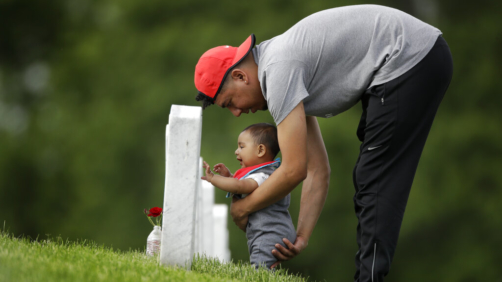 Angel Garcia-Metcalf steadies his seven-month-old son Angel as they visit the boy's great-grandfather's grave at Leavenworth National Cemetery Saturday, May 23, 2020 in Leavenworth, Kan. They were among a handful of people who decided to visit to the cemetery today instead of Memorial Day to beat the crowd and minimize the chance of catching COVID-19. (AP Photo/Charlie Riedel)