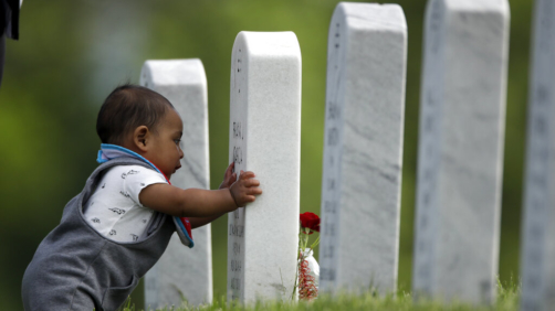Seven-month-old son Angel Garcia-Metcalf looks at his great-grandfather's grave as he visits Leavenworth National Cemetery with his parents Saturday, May 23, 2020 in Leavenworth, Kan. They were among a handful of people who decided to visit to the cemetery today instead of Memorial Day to beat the crowd and minimize the chance of catching COVID-19. (AP Photo/Charlie Riedel)