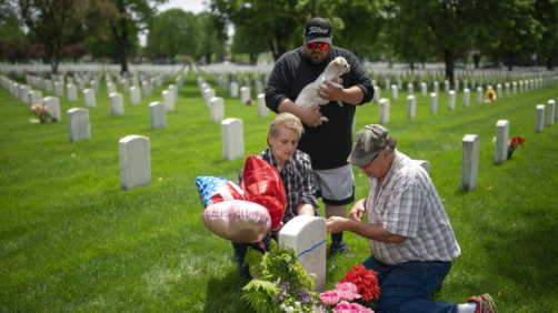 Teresa Baron places flowers and balloons at the headstone of her father, World War II Navy veteran Frank Baron, Sunday, May 24, 2020, at Fort Snelling Cemetery in Bloomington, Minn., during Memorial Day weekend. Teresa Baron's mother' and sister's remains are also buried at the cemetery. Her son Eddie Baron holds their dog