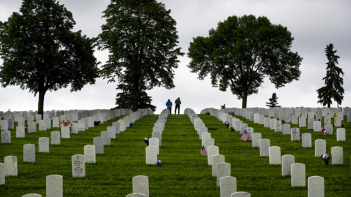 People pay their respects at graves of loved ones at Fort Snelling Cemetery on Memorial Day weekend, Sunday May 24, 2020, in Bloomington, Minn. (Jerry Holt/Star Tribune via AP)