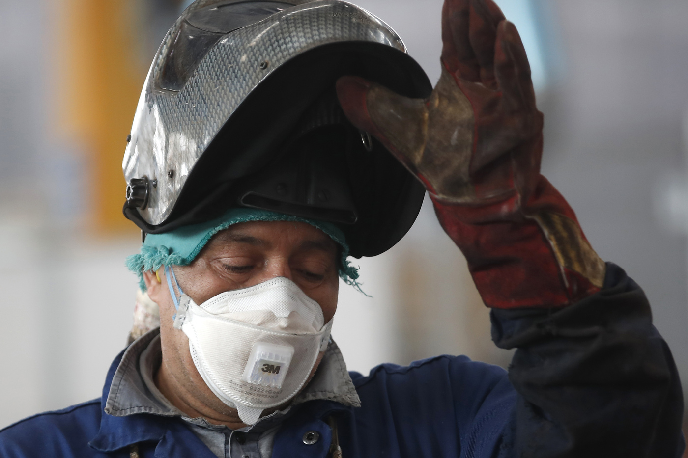 A man wears a safety mask under the soldering mask as he works at MAP, a factory operating in design, manufacture and installation of steel structures for civil and industrial use, in Corsico, near Milan, Italy, Wednesday, May 6, 2020. Italy began stirring again after the coronavirus shutdown, with 4.4 million Italians able to return to work and restrictions on movement eased in the first European country to lock down in a bid to stem COVID-19 infections. (AP Photo/Antonio Calanni)