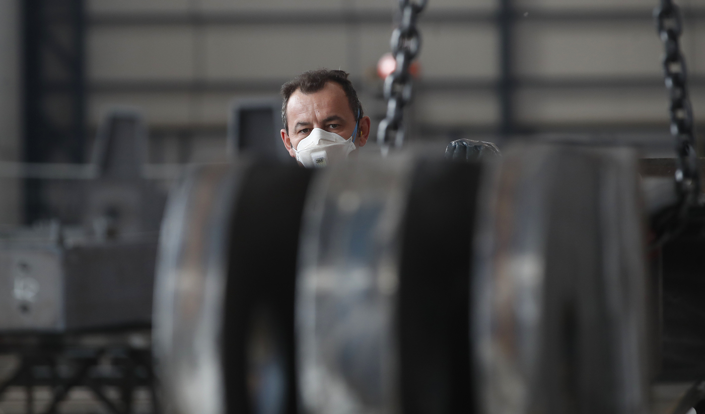 A man works at MAP, a factory operating in design, manufacture and installation of steel structures for civil and industrial use, in Corsico, near Milan, Italy, Wednesday, May 6, 2020. Italy began stirring again after the coronavirus shutdown, with 4.4 million Italians able to return to work and restrictions on movement eased in the first European country to lock down in a bid to stem COVID-19 infections. (AP Photo/Antonio Calanni)