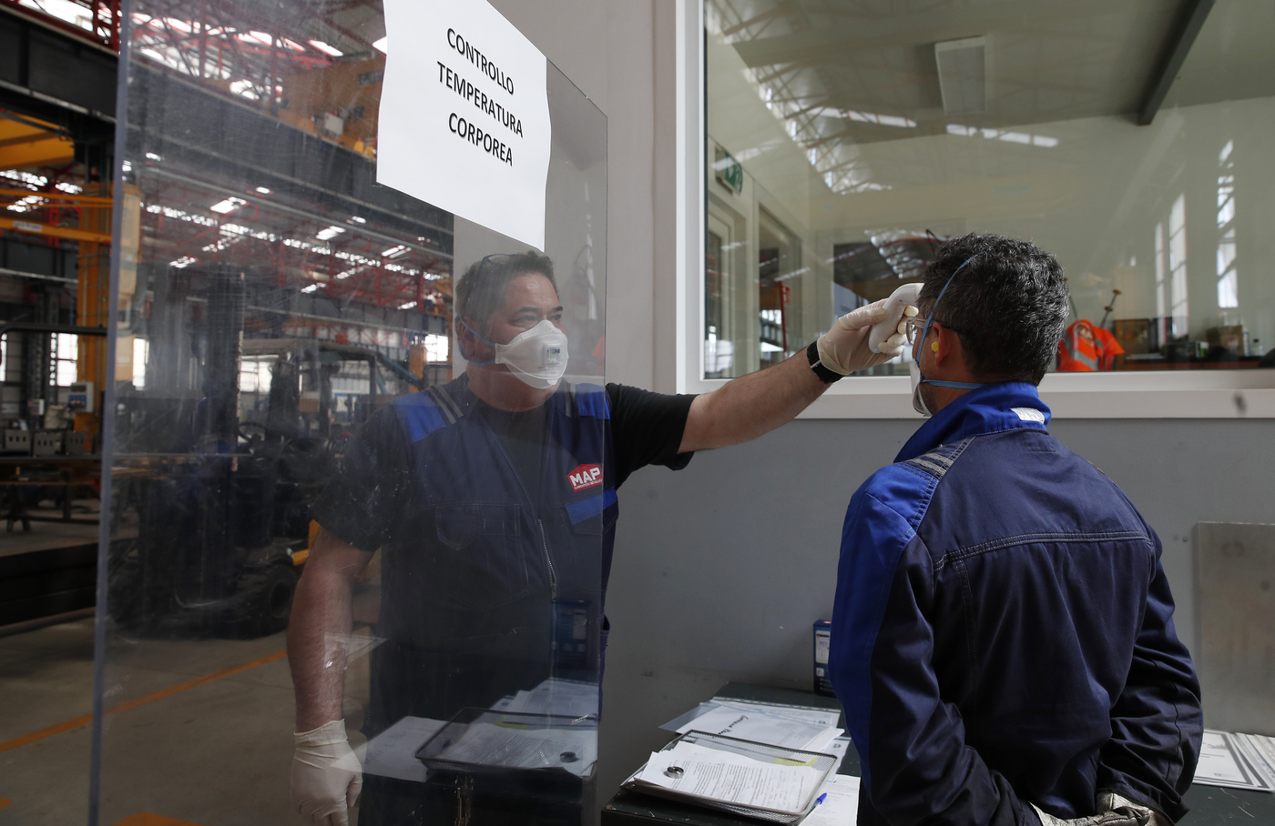 Body temperature is scanned at the entrance of MAP, a factory operating in design, manufacture and installation of steel structures for civil and industrial use, in Corsico, near Milan, Italy, Wednesday, May 6, 2020. Italy began stirring again after the coronavirus shutdown, with 4.4 million Italians able to return to work and restrictions on movement eased in the first European country to lock down in a bid to stem COVID-19 infections. (AP Photo/Antonio Calanni)