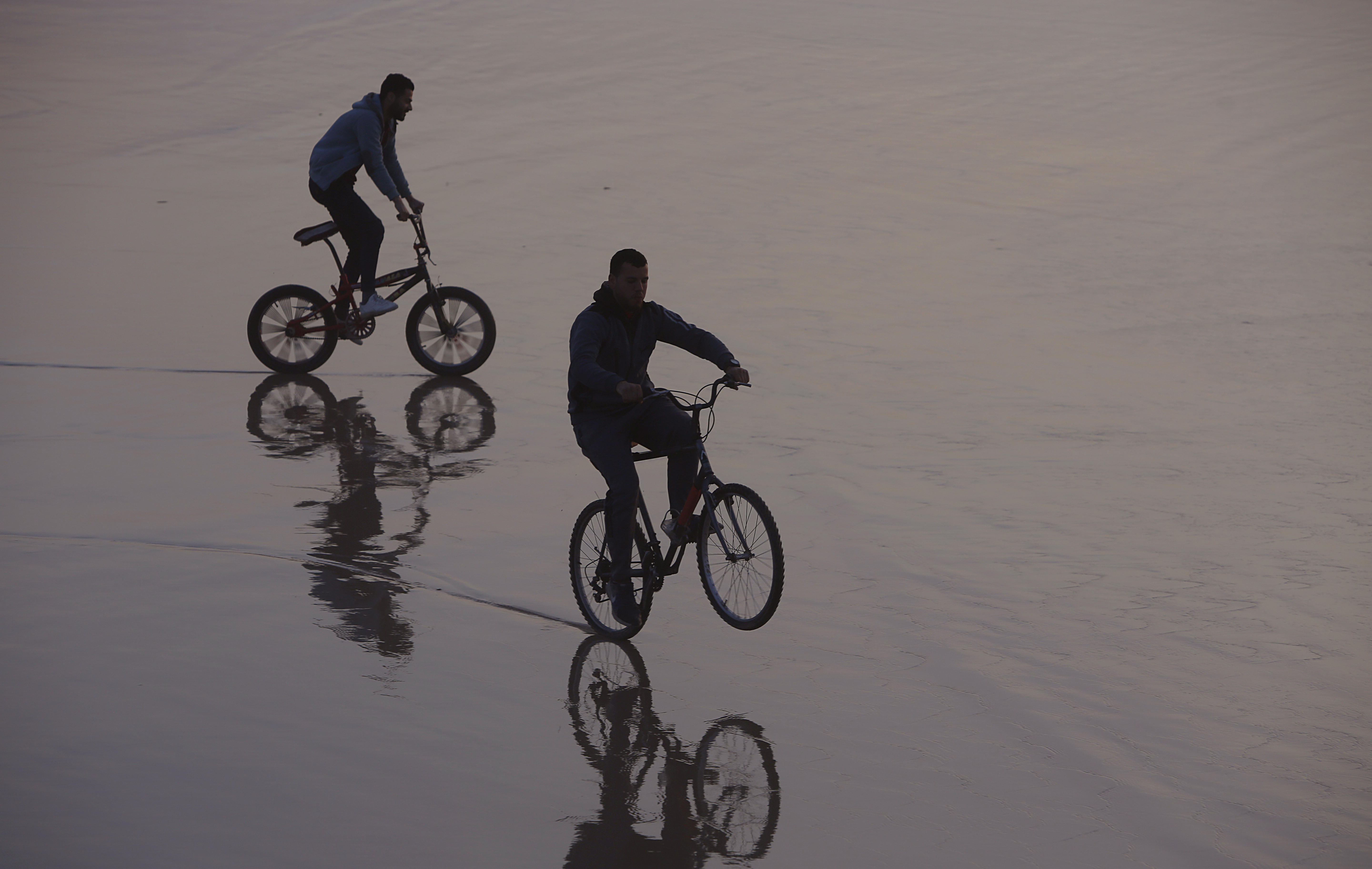 Palestinians ride their bicycles during the sunset at the beach, in Gaza City, Saturday, Feb.22, 2020. The beach is one of the few open public spaces in this densely populated city. (AP Photo/Hatem Moussa)