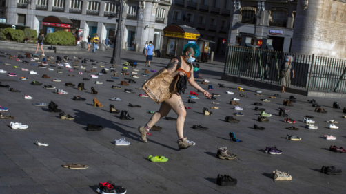 A member of the Extinction Rebellion group walks among shoes during the performance