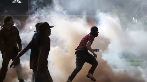 Protestors throw smoke bombs back at the Shelby County Sheriff's deputies Sunday, May 31, 2020, during a protest over the death of George Floyd on May 25. (Jim Weber/Daily Memphian via AP)
