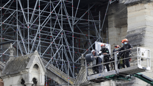 Workers are lifted Notre Dame cathedral, Monday, June 8, 2020 in Paris. Workers suspended from ropes will be lowered into the charred remains of scaffolding that melted atop Notre Dame when the cathedral went up in flames and begin the delicate job of dismantling the 200 tons of metal. (AP Photo/Thibault Camus)