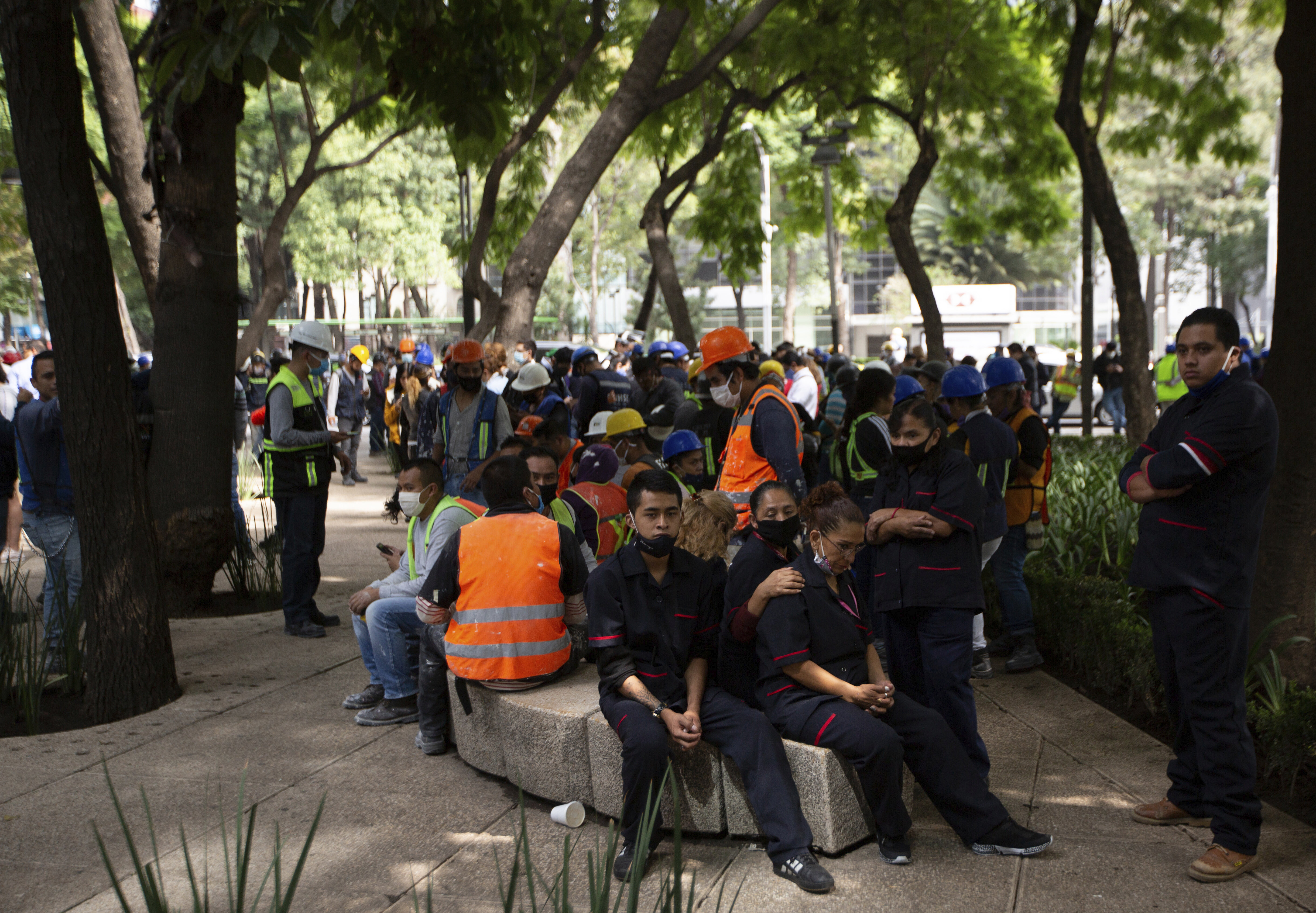Employees gather outside of their work building after a 7.5 earthquake, in Mexico City, Tuesday, June 23, 2020. The earthquake centered near the resort of Huatulco in southern Mexico swayed buildings Tuesday in Mexico City and sent thousands into the streets.(AP Photo/Fernando Llano)