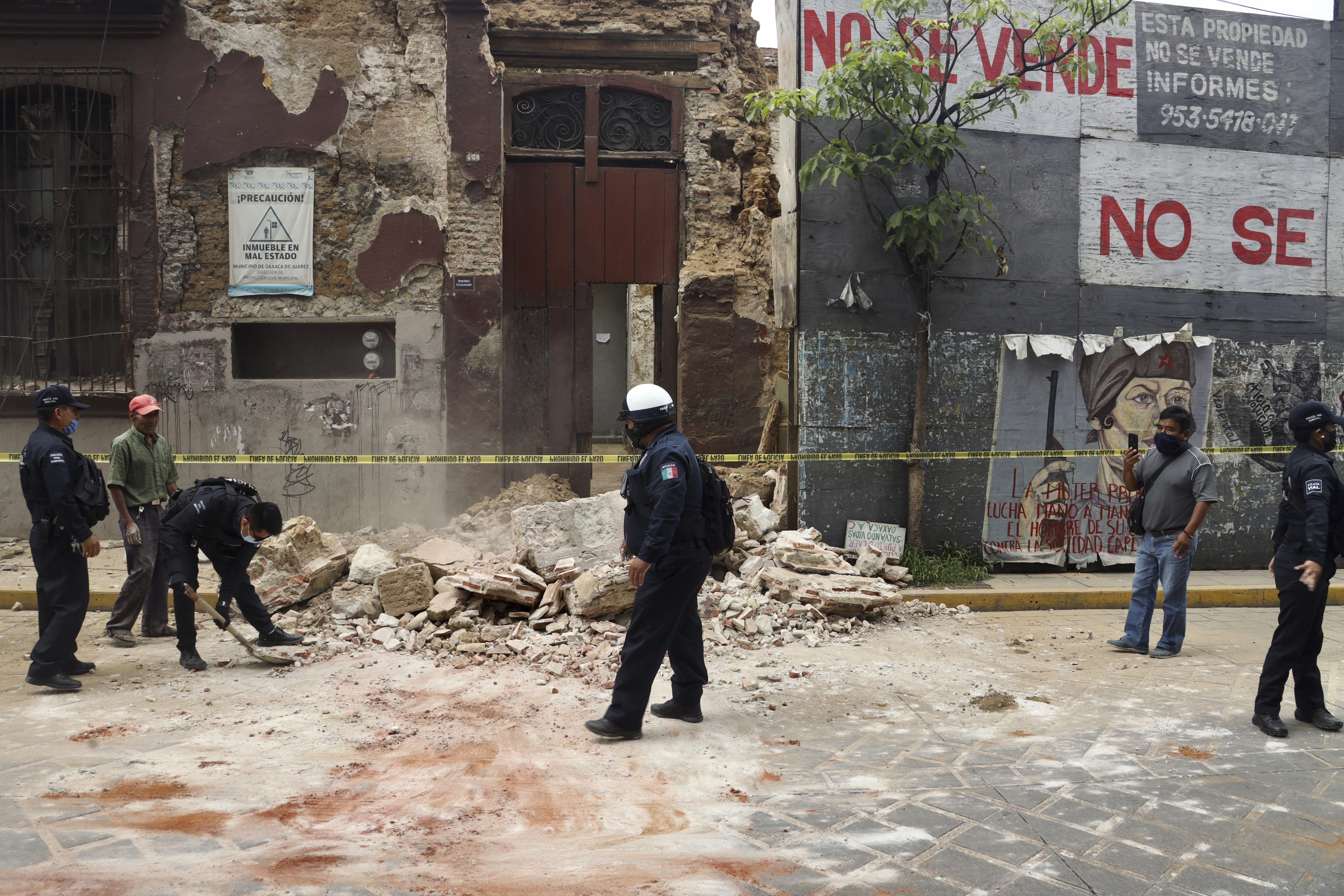 A policeman removes rubble from a building damaged by an earthquake in Oaxaca, Mexico, Tuesday, June 23, 2020. The earthquake was centered near the resort of Huatulco, in the southern state of Oaxaca. (AP Photo/Luis Alberto Cruz Hernandez)