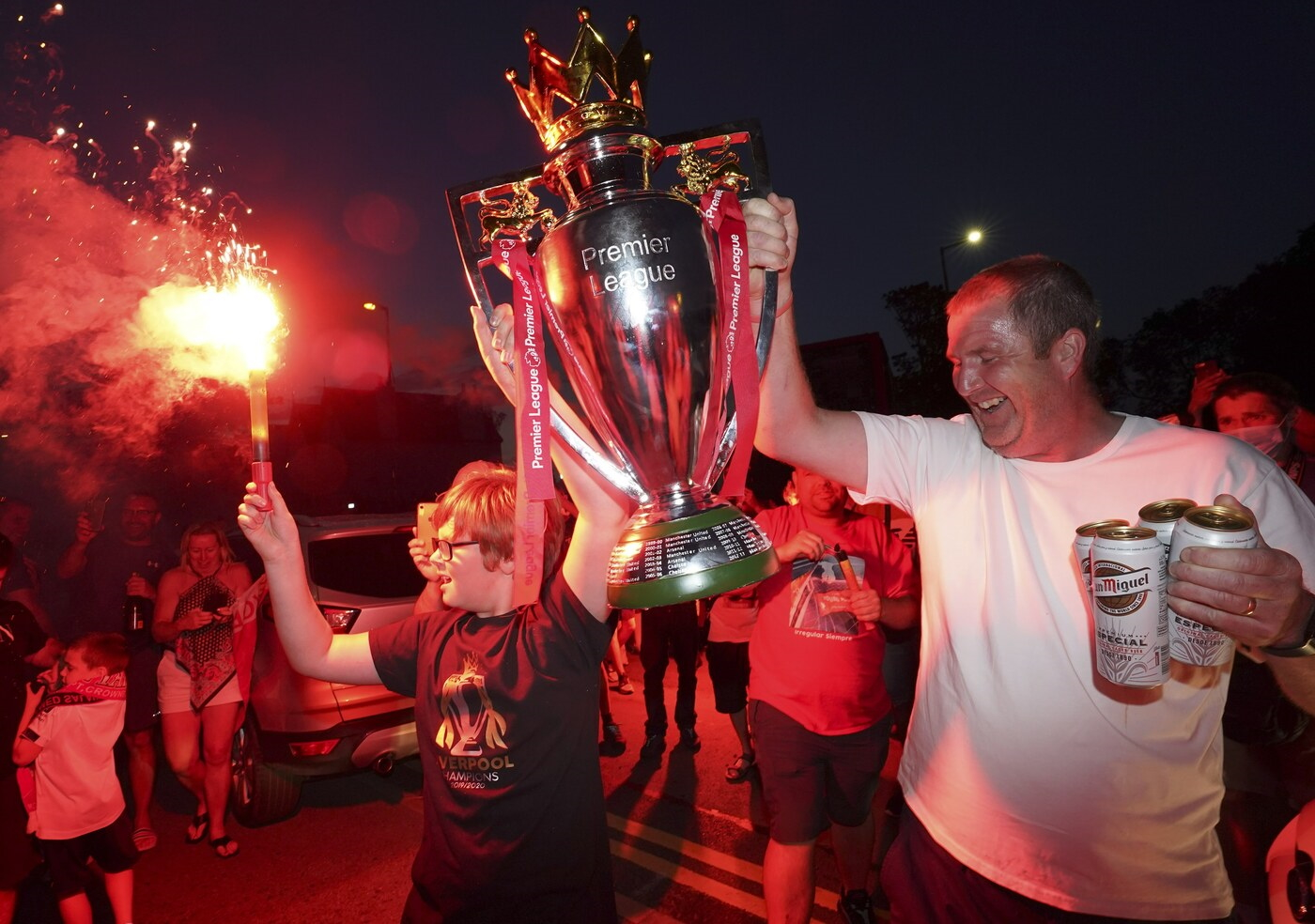 Liverpool supporters hold a replica Premier League trophy as they celebrate outside of Anfield Stadium in Liverpool, England, Thursday, June 25, 2020 after Liverpool clinched the English Premier League title. Liverpool took the title after Manchester City failed to beat Chelsea on Wednesday evening. (AP photo/Jon Super)