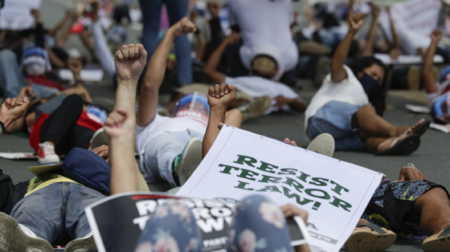 Protesters raise their clenched fists as they lay on the streets during a rally against the anti-terror law at the University of the Philippines in Manila, Philippines on Tuesday July 7, 2020. Philippine President Rodrigo Duterte recently signed a widely opposed anti-terror law which critics fear could be used against human rights defenders and to muzzle dissent. (AP Photo/Aaron Favila)