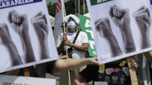 A man stands beside slogans during a rally against the anti-terror law at the University of the Philippines in Manila, Philippines on Tuesday July 7, 2020. Philippine President Rodrigo Duterte recently signed a widely opposed anti-terror law which critics fear could be used against human rights defenders and to muzzle dissent. (AP Photo/Aaron Favila)