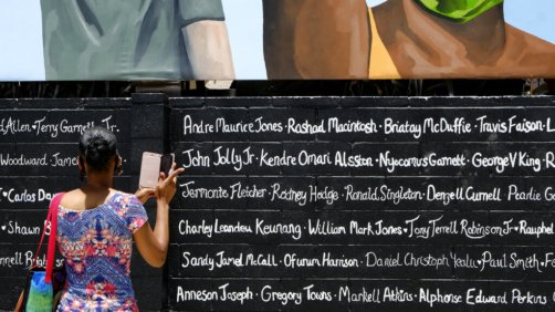 Artist Amanda Ferrell Hale takes a photo of some of the names under a section of a mural she collaborated in as part of a 148-foot tribute mural to Black Lives Matter at the unveiling in Los Angeles on Tuesday, July 7, 2020. The artwork was created by five African American artists, Alexandra Allie Belisle, PeQue Brown, Noah Humes, and Shplinton. Said to be the largest in the nation the mural was commissioned by Los Angeles Fourth District Councilmember David Ryu and the Laugh Factory. (AP Photo/Richard Vogel)