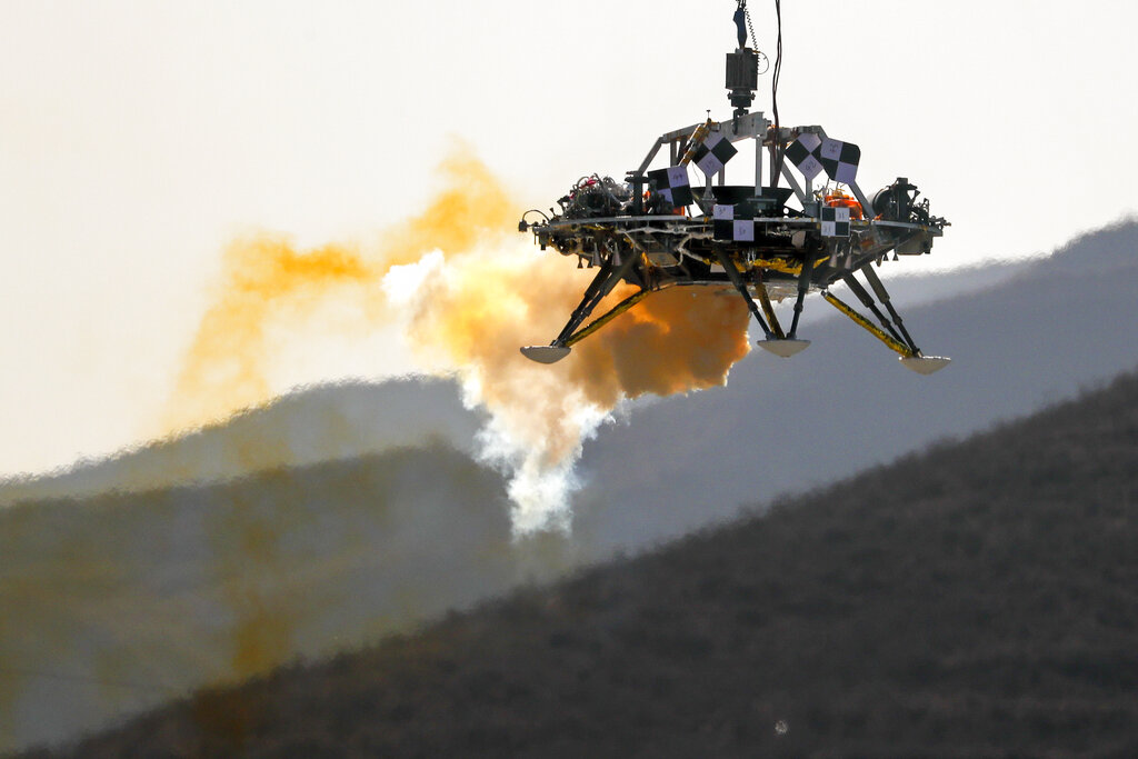 FILE - In this Thursday, Nov. 14, 2019 file photo, the Mars lander's hovering, obstacle avoidance and deceleration capabilities are tested at a facility at Huailai in China's Hebei province. China will launch their Mars rover and an orbiter sometime around July 23, 2020, in a mission named Tianwen, or Questions for Heaven. (AP Photo/Andy Wong)