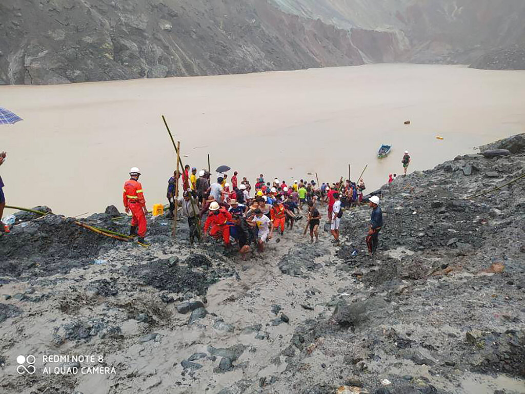 In this photo handed out from Myanmar Fire Service Department, rescue members and people carry bodies of of victims of a landslide from a jade mining area in Hpakant, Kachine state, northern Myanmar Thursday, July 2, 2020. Myanmar government says a landslide at a jade mine has killed dozens of people (AP Photo/Myanmar Fire Service Department)