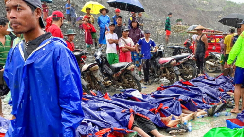 People walk and gather near dead bodies of jade scavengers who were killed in a landslide covered with plastic and lined up near a jade mining area Thursday, July 2, 2020, in Hpakant, Kachine state in northern Myanmar. Myanmar government says a landslide at a jade mine in the country's north has killed 50 people. The Ministry of Information cited the local fire service at the site of Thursday's landslide in Hpakant in Kachin state.(AP Photo/Zaw Moe Htet)