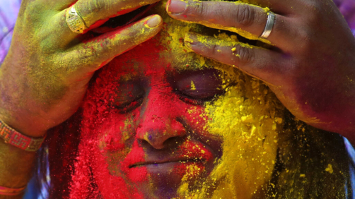 Face of a woman is smeared with colored powder during celebrations marking the Holi festival in Mumbai, India, Tuesday, March 10, 2020. Holi, the festival of colors heralds the arrival of spring (AP Photo/Rajanish Kakade)