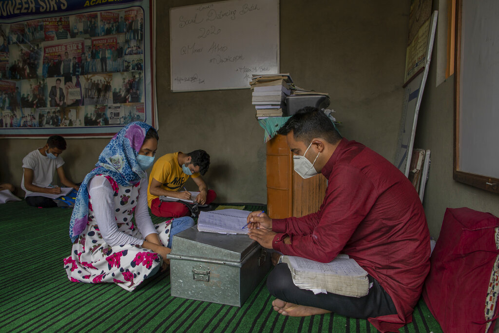 Iqra Nazir listens to her teacher Muneer Ahmed during a math coaching class in Srinagar, Indian controlled Kashmir, Wednesday, July 22, 2020. Decades of insurgency, protests and military crackdowns have constantly disrupted formal schooling in Indian-administered Kashmir, where rebels have fought for decades for independence or unification with Pakistan, which controls the other part of the Muslim-majority region. Over the years, volunteer-run community schools and makeshift classrooms have emerged to fill the gap when formal schools shut down, but large-scale troop deployments and restrictions on public movement mean they reach only a small proportion of students. (AP Photo/Dar Yasin)