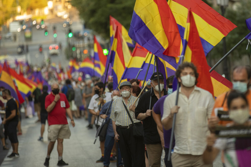 Demonstrators holding a Republican flag march during a protest against Spanish Monarchy in Madrid, Spain, Saturday, July 25, 2020.  A barrage of media leaks have revealed how the king's father, former monarch Juan Carlos I, allegedly hid millions of untaxed euros in offshore funds, prompting public protests. (AP Photo/Manu Fernandez)