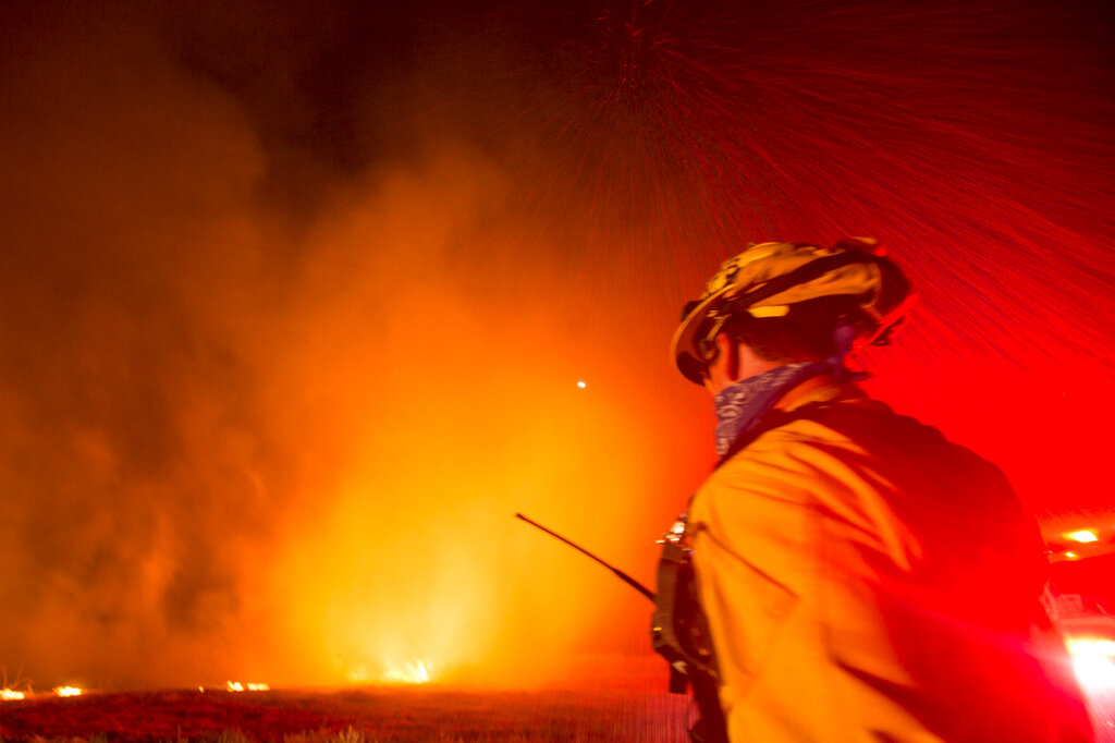 A firefighter watches as a helicopter drops water to the Apple Fire in Banning, Calif., Saturday, Aug. 1, 2020. (AP Photo/Ringo H.W. Chiu)
